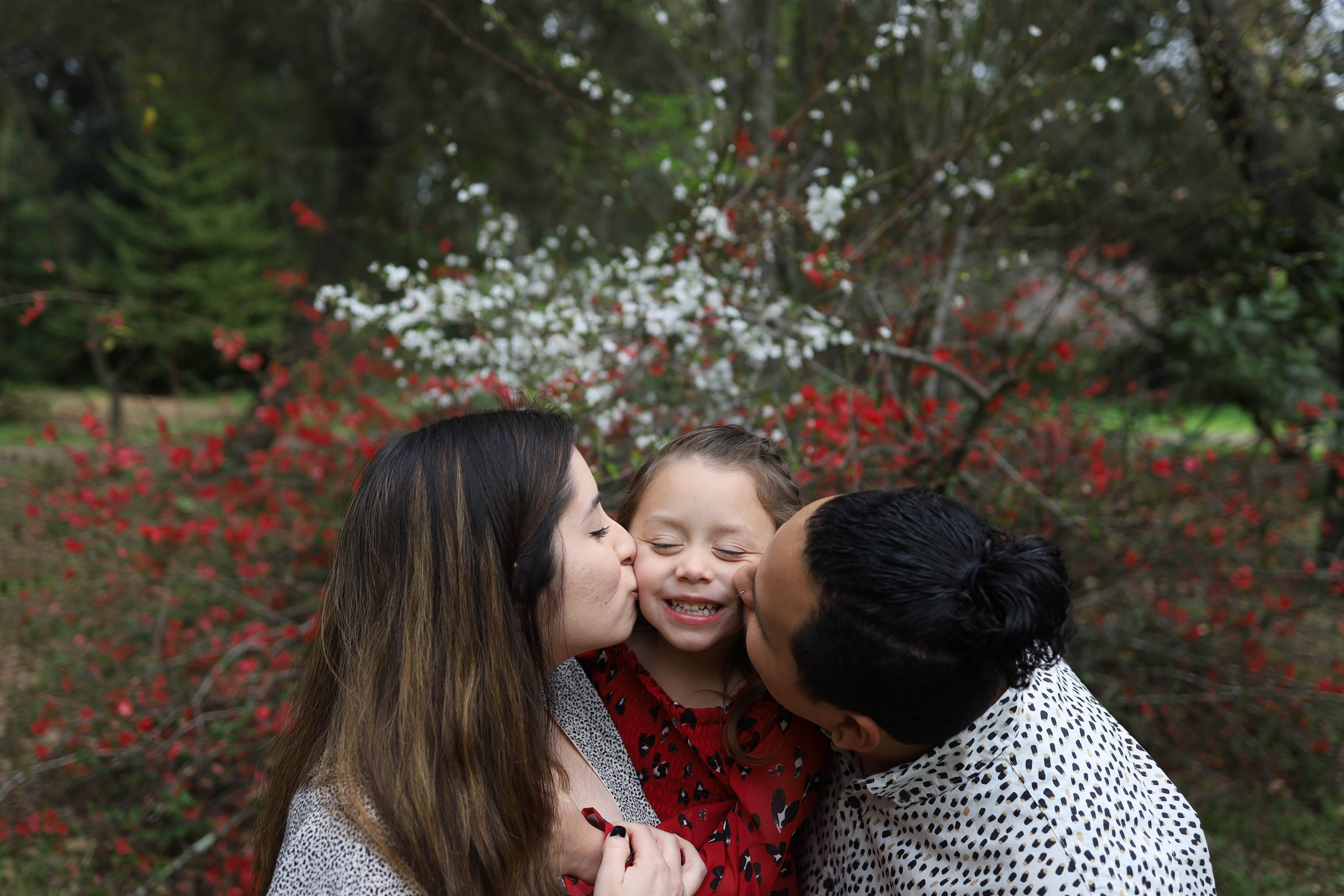 Penny being kissed on the cheek by her parents