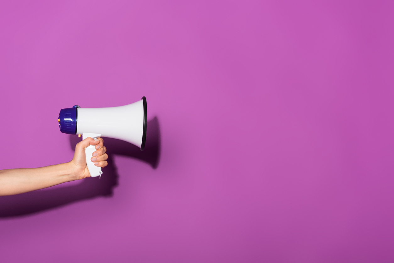 cropped image of woman holding megaphone on purple background